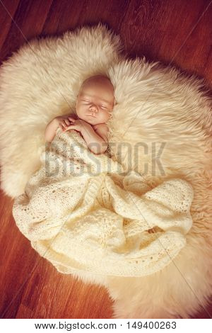 Sleeping newborn baby lying on white fur carpet covered with cream knitted blanket. The little boy fell asleep on the floor