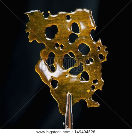 A piece of cannabis concentrate aka shatter isolated against black