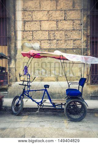 A Cuban rickshaw (bicitaxi) in old Havana street. Rickshaw are a popular way of transport in Cuba