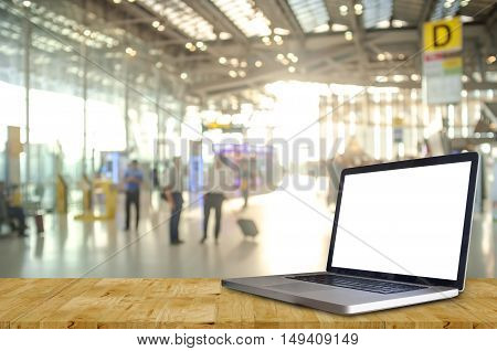 Laptop Showing Blank Screen with Blurred of Check in Counter and Passengers in a airport departure terminal.
