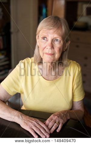 Serious Senior Woman Seated At Table