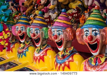Row of colourful clown heads in carnival side show alley with prizes