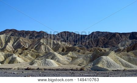 View of Death Valley, California, USA, with sand dunes and, in the background mountains. Wild and arid landscapes. Light, natural colors.
