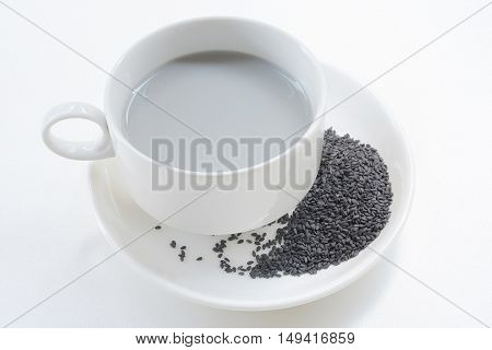 Soya milk and black sesame seeds in cup on white background