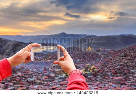 Smartphone photographing top view monastery at Larung gar (Buddhist Academy) in sunset time Sichuan China