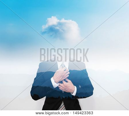 Double exposure businessman with cloud instead of head, on blue sky with silhouette mountains