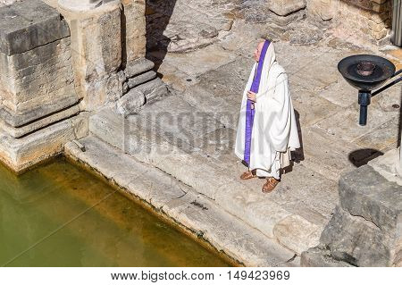 Bath UK - August 15 2015: Actor playing the role of an old roman citizen. The Roman Terms complex is a site of historical interest in the English city of Bath. The Baths are a major tourist attraction