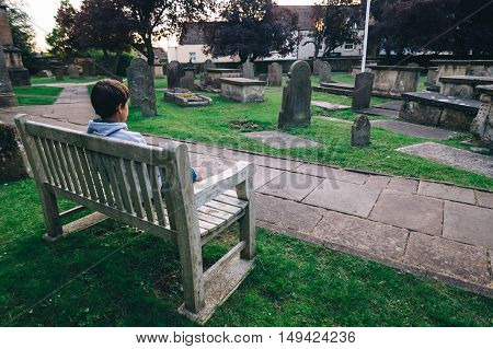 Tetbury UK - August 15 2015: Lonely young sitting on a wooden bench in the churchyard of St. Mary The Virgin church. Sunset
