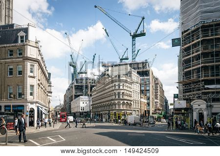 LONDON UK - AUGUST 21 2015: Queen Victoria street in the city of London with people crossing the street and the construction of a new office building with cranes