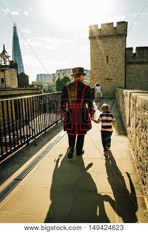 LONDON UK - AUGUST 21 2015: Yeoman warder and son in the Tower of London. The Yeomen Warders are popularly known as the Beefeaters and are ceremonial guardians of the Tower of London.