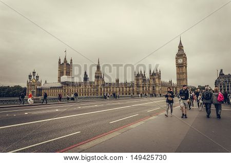 London UK - August 18 2015: Big Ben and Parliament Houses from Westminster Bridge a cloudy day of summer while some tourist are walking on the bridge. London is one of the most visited cities in the world.