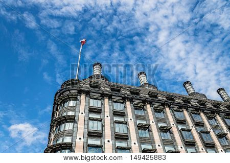 London UK - August 19 2015: Low angle view of Portcullis House in London with the Union Jack flag against blue sky and white clouds near Westminster Palace.