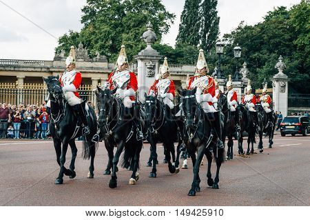 London UK - August 19 2015: Queen's Guards cavalry parade during traditional Changing of the Guards ceremony at Buckingham Palace. This is one of the most popular tourist attractions in London.