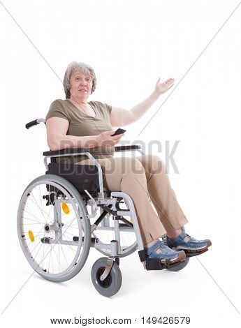 Senior sitting in wheelchair pointing to the side while holding smart phone. All on white background.