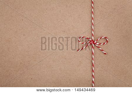 Christmas or New Year string or twine tied in a bow on kraft paper texture. Gift or present concept. poster