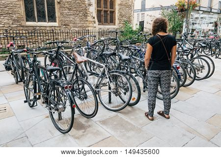 CAMBRIDGE UK - AUGUST 11 2015: Young woman in a parking for Bicycles in Cambridge with steel bars to lock bikes to. Cambridge is a university city and one of the top five universities in the world.