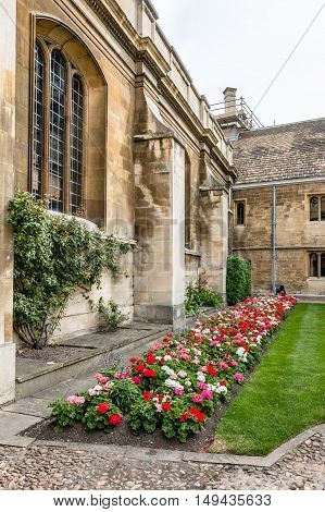 CAMBRIDGE UK - AUGUST 11 2015: Courtyard with flowers in the Gonville & Caius College in the University of Cambridge. Cambridge is a university city and one of the top five universities in the world.