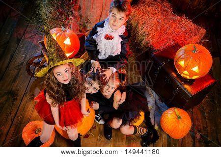 Cheerful children in halloween costumes celebrating halloween in a wooden barn with pumpkins. Halloween concept.