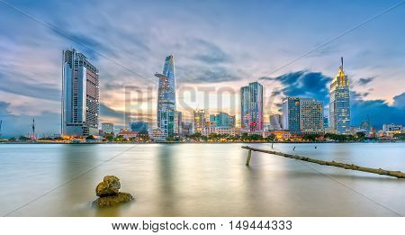 Ho Chi Minh City, Vietnam - September 23rd, 2016: Riverside City sunset brighter coal sparkling skyscrapers along river, foreground a small bridge urban toward honoring development city at night