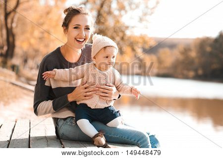 Happy mother holding baby girl 1 year old wearing knitted sweaters sitting on wooden pier in autumn park. Looking away. Happiness.