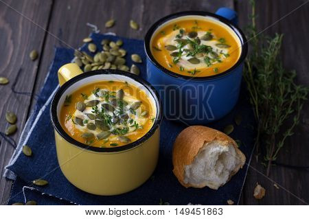 Pumpkin soup with cream, pumpkin seeds and thyme in the colored cups on a wooden surface
