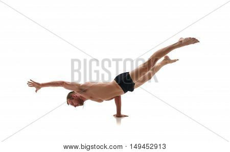 Sport. Studio photo of male athlete doing handstand. Isolated on white