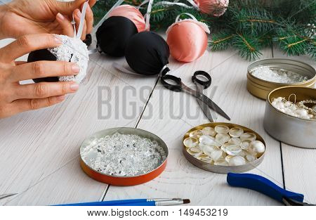 Creative diy hobby. Making handmade craft black stylish christmas balls with lace. Woman's leisure, tools for creating holiday decorations. Female hands closeup working on white wooden table