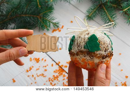 Creative diy craft hobby. Woman shows craft christmas ball with felt spruce tree and empty wooden lable with copy space. Home leisure, holiday decorations. Closeup of female hands at wood background