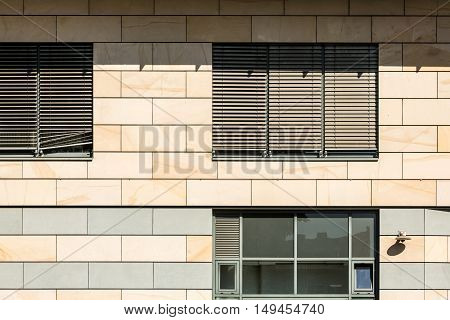 Detail of a facade with windows and roller shutter