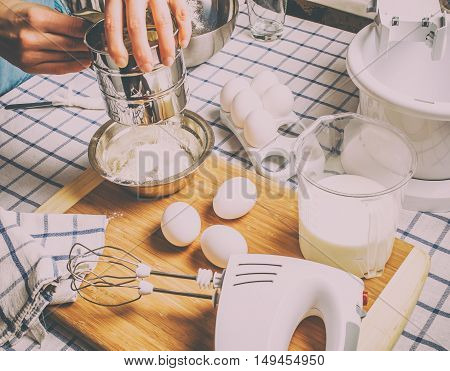 Sift flour man standing behind a table on which the chef prepared ingredients for a batch of pancakes and cake dough.
