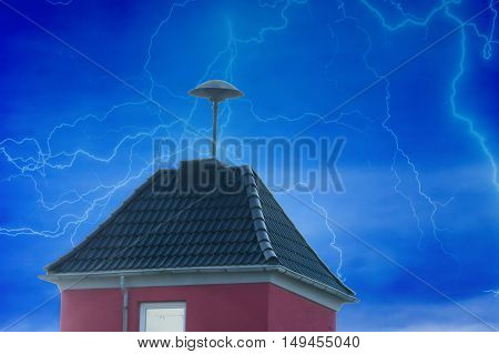 Flashes over a small residential tower with Air Raid Siren on the roof in front of dramatic sky.