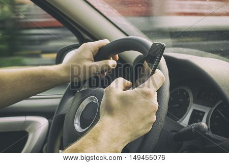 man is driving a car and holding a mobile phone near the steering wheel