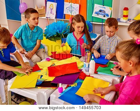 Group of children are making something out of colored paper on table in primary school. Children craft lesson in primary school.