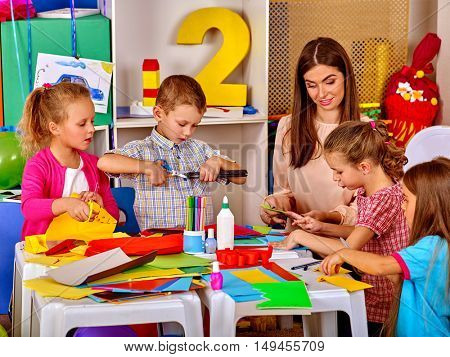 Group children with teacher are making something out of colored paper on table in primary school. Children craft lesson in primary school.