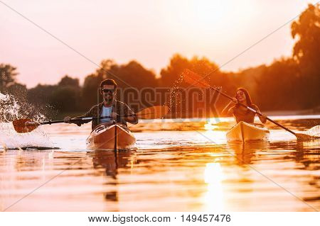 Spending great time on river. Confident young couple kayaking on river together with sunset in the backgrounds