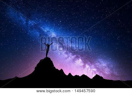 Landscape with Milky Way. Colorful night sky with stars and silhouette of a standing happy woman with raised-up arms on the mountain peak on the background of beautiful galaxy. Blue milky way rocks