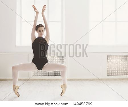 Classical Ballet dancer side view. Beautiful graceful ballerine in black practice ballet plie positions near large window in light hall. Ballet class training, high-key soft toning, copy space