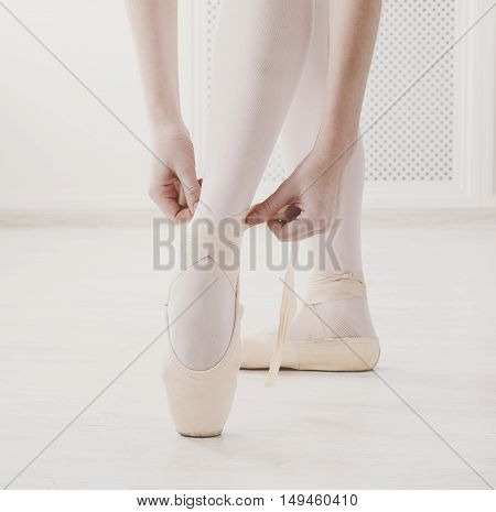 Closeup legs of young ballerina who puts on pointe shoes at white class room background. Ballet practice on training. Beautiful slim graceful feet of ballet dancer, unrecognizable female.