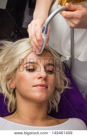 Laying woman getting laser and ultrasound facial therapy in spa salon