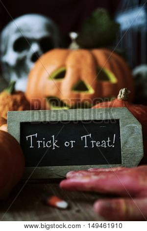 a chalkboard with the text trick or treat, surrounded by some different pumpkins, placed on a rustic wooden surface, and some scary ornaments, such as an amputated hand, a skull or a carved pumpkin