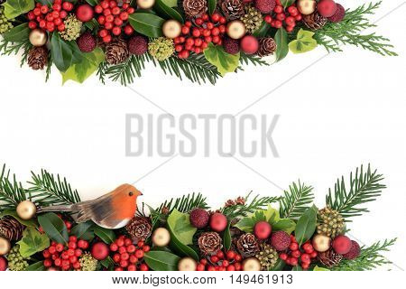 Christmas decorative floral background border with red and gold bauble and robin decorations, holly, ivy, pine cones , cedar cypress and fir leaf sprigs over white with copy space.