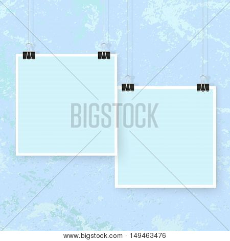 Posters on binder clips on blue grunge wall. Square paper mockups set. Modern trendy framing for your design. Vector template for picture painting drawing quotes poster or photo.