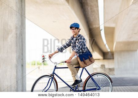 people, style, leisure and lifestyle - smiling hipster man with shoulder bag riding fixed gear bike on city street