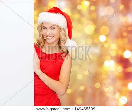 christmas, people, holidays and advertisement concept - happy woman in santa helper hat with blank white board over lights background