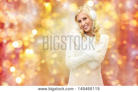winter, holidays, christmas and people concept - smiling young woman in earmuffs and sweater over lights background