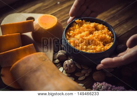 Pumpkin millet porridge with pumpkin in the background. Still life. eating pumpkin millet porridge with milk hands breakfast on a wooden background.