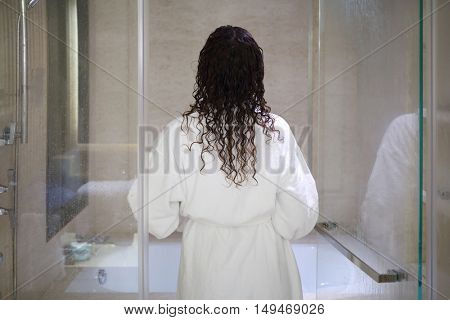 Woman in white bathrobe enters bathroom with glass doors, back view