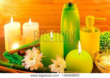 Green spa bath products concept with candles flowers bamboo