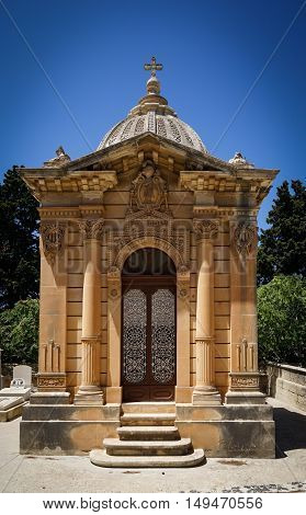 The old single family crypt on a blue sky background. Santa Marija Addolorata cemetery. Paola. Malta.
