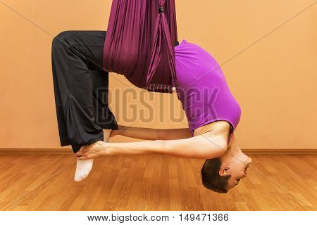Pregnant woman making aerial yoga exercises, indoor, fly yoga